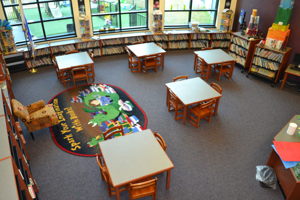 A private elementary school classroom filled with books and tables and chairs