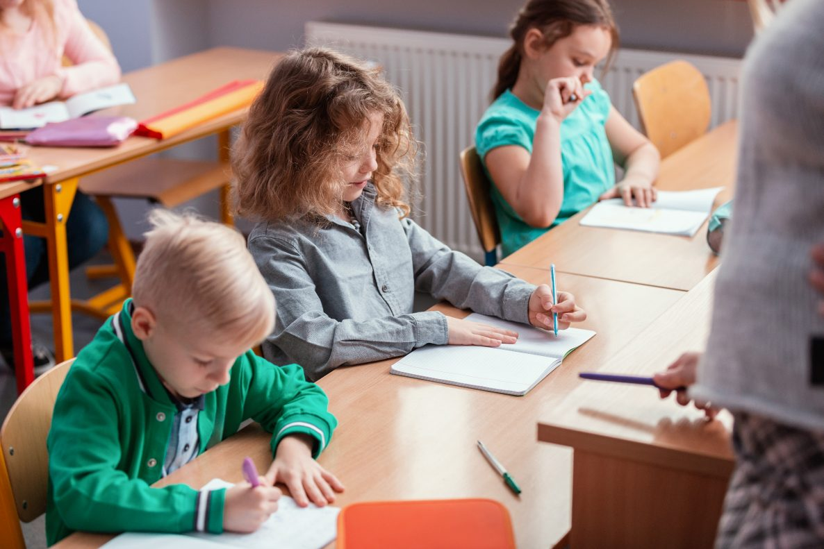 Children sit at the tables in the classroom and studying