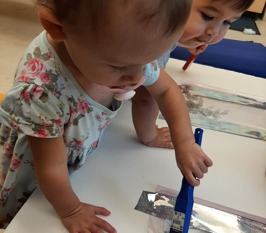 Two toddlers playing with magnet pins